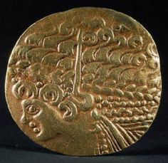 Gold coin of the Celtic Ambiani tribe of northern Gaul (France). It shows Apollo with laurelled hair and dates from the 2nd century B.C.