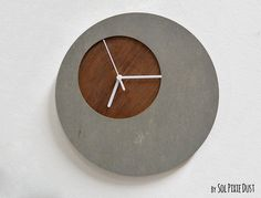 """Concrete Circle Wall Clock With Wooden Hole - Modern Wall Clock. The clock is made of two layers, one of Concrete and one of Wood ❂ Concrete Sheet 0.23""""- 6 mm ❂ PLY Oak Wood 0.16"""" - 4 mm / Varnish With Dark Oak Satin ❂ My clock mechanisms are EZ Quartz® Sweep (Non Ticking - Silent) and RoHS Approved! ❂ Requires 1 AA battery (not included)."""