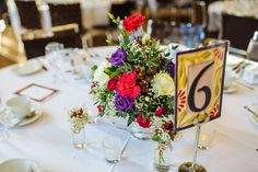 Bright red, purple & white flower table centre piece - Image by James & Leanne Wedding Photographers - A gay wedding in Leeds city centre with bright colour scheme and club style reception