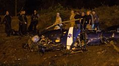 Police gather at a military helicopter which crashed in Rio de Janeiro, Brazil on Saturday, Nov. 19, 2016.