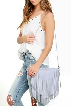 """Create a fiery hot look with the Phoenix Flight Grey Fringe Clutch! Grey blue faux leather features braided details and tiers of fringe across a rectangular design with silver zipper top. Fabric-lined interior has a three side wall pockets. Carry as a clutch or attach the 46"""" chain strap."""