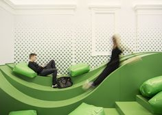 Wavy green lounge by Svet Vmes. Slovenian firm Svet Vmes Architects has converted an unused entrance of a school in Ljubljana into an undulating green lounge featuring spotty walls and big cushions. The defunct second entrance was transformed into a space where students can relax and socialise, which they named School Landscape.