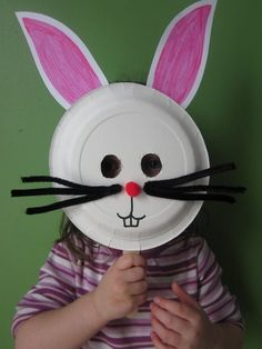 {Mia models my bunny mask.} Materials: paper plate craft stick white paper scissors tape glue red or pink pom pom pink and black m. Minion Easter Eggs, Easter Bunny Ears, Paper Plate Masks, Paper Plate Crafts, Paper Plates, Bunny Crafts, Easter Crafts For Kids, Easter Activities, Preschool Crafts