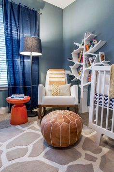 Sweet boy's nursery features blue walls accented with navy blue curtains, Land of Nod Blue Canvas Curtain Panels, as well as art over white crib, Oeuf Sparrow Crib, beside Land of Nod White Leather Joya Rocker accented with striped throw blanket paired with Land of Nod Light Years Grey Floor Shade and Graphite Base, West Elm Martini Side Table and brown leather Moroccan pouf situated in front of Nursery Works Tree Bookcase atop white and gray giraffe rug layered over gray carpeting.