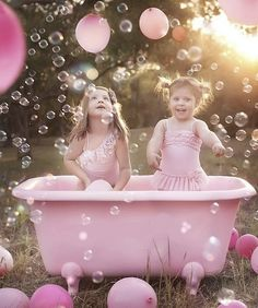 kids playing with bubbles in a pink clawfoot tub