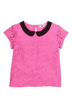 Top met kant: Een tricot top met een met kant bekleed voorpand, een claudinekraagje, een splitje met een knoop in de nek en korte, kanten mouwen.