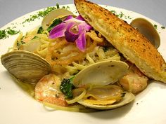 Shellfish Pasta - Sauteed Shrimp and Steamed Clams in a Garlic Herb Broth. Tossed with Spinach, Caramelized Onions and Fresh Herbs. Served over Linguini. - see more featured Fresh Catch menu items at Reel Seafood Co. - www.reelseafoodco.com/menu/fresh-catch