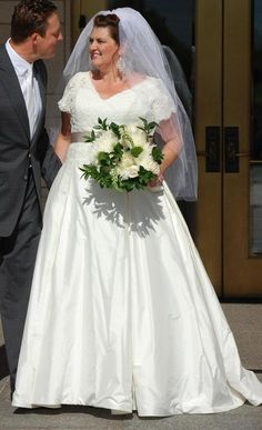 Short sleeve plus size bridal gowns can be modest.  This v neck wedding gown has an a-line cut skirt.  There is a ribbon sash at the waist. We are in the USA and can produce custom #plussizeweddingdresses that are affordable and still stylish.  See more short sleeve plus size wedding dresses at http://www.dariuscordell.com/featured_item/plus-size-wedding-dresses-bridal-gowns/