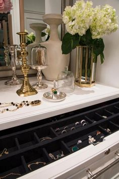 Discreet drawers store jewelry and other valuables, while an elegant vanity offers display space for decorative and functional accessories, including a silver and glass cloche that keeps necklaces and bracelets on display.