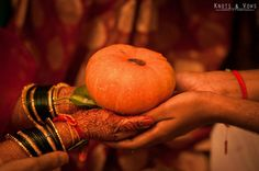 Pumpkin with a coin being presented the the bride. #knots and vows photography #wedding photographer mumbai #mumbai wedding photography #hindu weddings #indian weddings