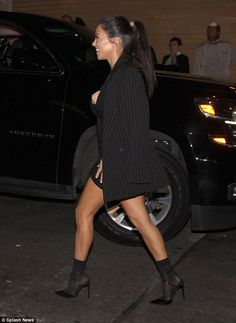 Bright spirits: A huge smile on her face, she accented the look with a pair of black stiletto boots and had flung a striped black blazer casually over her shoulders