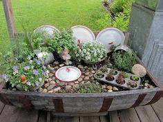 Fairy garden in a wine barrel from organizedclutter.net