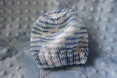 This is a very basic baby hat pattern with a ribbed bottom, stockinette body and neatly decreased crown. It is worked in the round so that it is seamless.