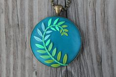 Polymer clay pendant with green and blue leaf pattern. $44.00, via Etsy.