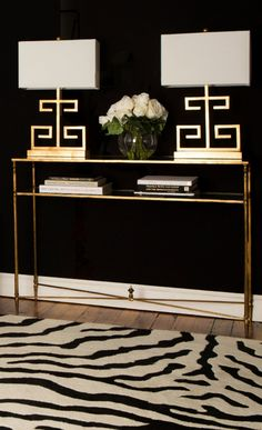 Metallic brass lamps give a luxe and opulent look against the intense black wall