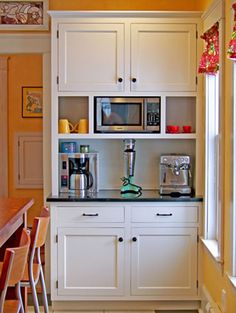 Frame out cabinets to completely hide the microwave - maybe hide mixer, toaster & coffee maker too?