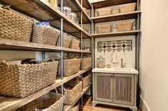French kitchen pantry features reclaimed wood shelving unit filled with woven baskets alongside gray cabinets with metal mesh doors topped with white marble framing prep sink.