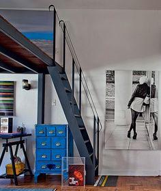 O apartamento do fotógrafo Lufe Gomes tem um mezanino com a cama. Sob ele, fica o escritório, com o armário azul debaixo da escada metálica