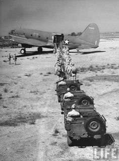 Curtiss C-46 cargo plane loading troops and jeeps, 1942.