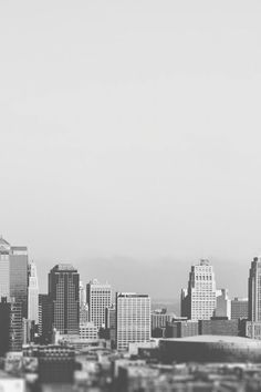 This black and white picture shows the downtown and business district of a typical american city. Some medium sized sky scrapers, some low-rise buildings and a stadium are visible. The background seems to be foggy.