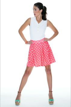 Our grapefruit slice print looks like polka dots from a distance.  Bailey is wearing our pleated golf skort with shorts built in and pockets in the pleats.  Fabric is moisture wicking and has sun protection #golf #skort #golfoutfit