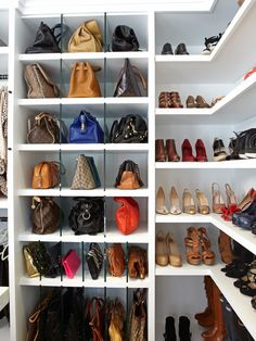 Chic closet with white built-in shelving featuring glass dividers holding purses and open shelving holding shoes.