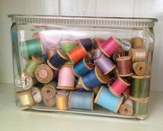 a jar of vintage sewing thread in all colors of the rainbow. Shown in an antique glass battery jar.