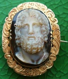 Zeus      Agate, gold  Size of the cameo: 1 1/4 x 15/16  Size of the frame: 1 5/8 x 1 1/4  Date and origin of the cameo: Italy, ca 1780  The frame is English, ca 1860-1880  Condition: mint. Veins by origin.       Museum quality cameo, crisply carved in high relief to depict Zeus.