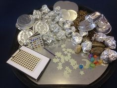 Space themed tuff spot for EYFS. Includes pebbles sprayed with glitter, stones wrapped in foil, scrunched up fool 'moon rocks', glow in the dark stars, gravel, clipboard with paper and star stickers, foil containers and toy planets. All in a mirrored tuff spot.