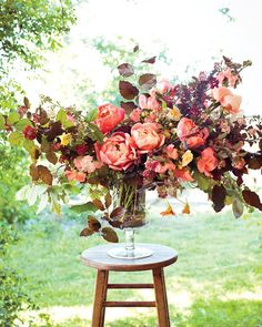 """I love walking in the garden first for inspiration. I like to see how closely I can mimic in the vase what I find there,"" she says. In this tall glass urn, she started with a base of copper beech and ninebark branches, anchored by a large flower frog, before adding 'Coral Charm' peonies, 'Ghislaine de Féligonde' roses, sweet peas, nasturtiums, raspberries, and Sanguisorba."