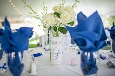 Blue and white wedding colors...All white center piece with blue linens and accents. White hydrangea & white dendrobium orchids. For center piece you can DIY : flowers from premium blooms online. 3-4 orchids stems in bottom of the vase..kind of floating in water. 4-5 hydrangeas with 4-5 more orchids coming out.  Custom luminaries can be printed off on rice paper. Fold around small candle.