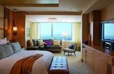 Ritz-Carlton Suite bedroom with plush bed, seating area and views of the city