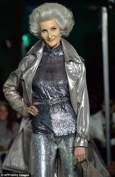 a cool and confident woman pulls off all over space-age silver - lame trench, sequin top and leggings and cinching belt - to match her bouff...