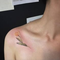 Yellow tulip tattoo on the shoulder.