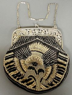 """Ladies late 19th c. purse with black and silver thread embroidered body, a silver frame and chain, the frame marked """"Made in Italy"""" and with ornate grotesque mask and serpent-form griffin decoration. 8.5""""x8.5"""""""