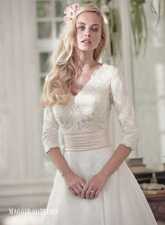Brentleigh wedding dress by Maggie Sottero | Demure and sophisticated, this elegant A-line wedding dress offers a gorgeous lace bodice, pleated Romance satin belt at the waist, and soft Vicenza organza skirt. Three-quarter sleeves lend a demure alternative to a bare shoulder. Finished with V-neckline and covered buttons over zipper and inner elastic closure.