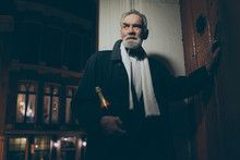 Man in tuxedo with bottle of champagne knocking on door at night