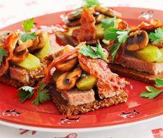 Inget kan vara godare till brunch än dessa danska smörrebröd med leverpastej, champinjoner och salt bacon! Lägg bara upp pastej, knaprigt fläsk, gurka och den nyfrästa svampen på ett mättande, grovt bröd och servera. En snabb och enkel måltid!