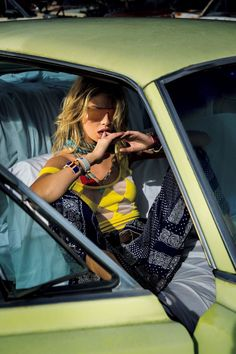 Posing in a car, Stella Maxwell wears yellow top with printed pants