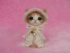 He encontrado este interesante anuncio de Etsy en https://www.etsy.com/es/listing/212386641/needle-felted-orange-tabby-cat-in-cape