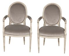 A pair of Louis XVI style fautueils.   Painted in a cream color with Grey velvet upholstery.  Early 19th century.  37 H x 22 W