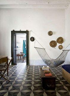 Baldosas antiguas, decoración simple y una hamaca que le da el toque relajado.