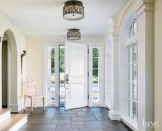 Basalt stone flooring, cut into squares and rectangles, connects the entry foyer with the exterior, where the stone is used in its natural geometric shape. The two custom-designed ceiling fixtures are from Lampworks in New York, and the decorative Ironware sconces are from John Rosselli & Associates.