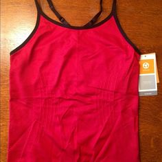 Champion women's seamless razorback sport top. Size medium women's seamless razorback sport top. Brand new, tags still attached. Nylon spandex blend with a sewn in sports bra insert. No padding. Champion Tops Tank Tops