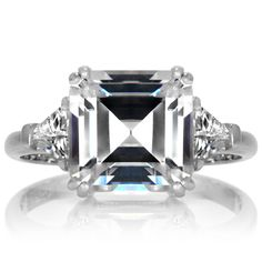 Pavé Must Have of the Day: 5 Carat Asscher-cut GIA-certified diamond held by double eagle prongs and complimented by two trilliant-cut side stones set in platinum. No.Words.Can.Describe.Pavé
