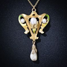 Consummate Art Nouveau curvaceousness is captured in this entrancing and sinuous lavaliere necklace, exquisitely sculpted in 18 karat yellow gold with four shimmering natural freshwater pearls and a splash of shaded yellow-green enamel. A graceful and artful beauty, circa 1900.
