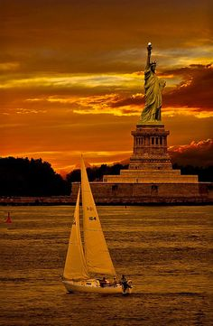Orange sky lights bathe Lady Liberty in the evening sky as a sailboat sails by the famous island. Photograph entitled LIBERTY credited to Aldo Costantini - DdO:) - Notice the brilliant point of light in the statue's torch.  Pinned via djferreira224