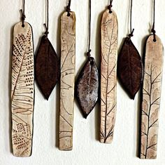 "I've created these beautiful natural wind chimes from brown stoneware clay and white porcelain. The cross bar is a stoneware ""branch"" with wood graining. It's been lightly stained to enhance the grain. The white chimes are porcelain and each impressed by various species of leaves that may include oak, fern, elm, and mulberry, leaves depend on seasonal availability. The fossil-like impression is gorgeously enhanced with an iron oxide wash."