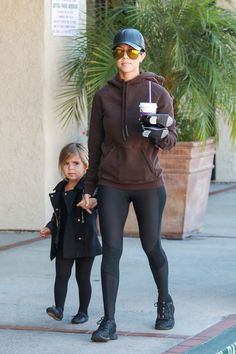 Kourtney Kardashian wearing Adidas Yeezy Originals by Kanye West Half Zip Hoodie in Mole, Skins Ry400 Recovery Long Tights, Westward Leaning Concorde 2 Sunglasses, Hat Attack Leather Baseball Cap