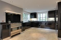 Matching range of high gloss black wall and base kitchen units with soft closure doors. Granite work surfaces